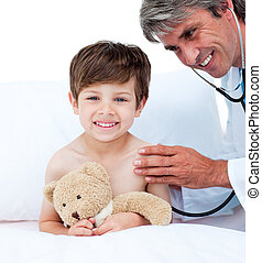 Mature doctor checking little boy\'s pulse