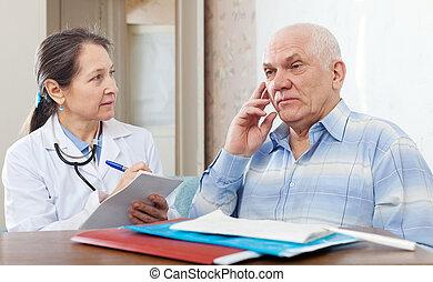 Mature  doctor examining the senior patient