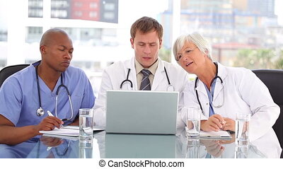 Mature doctor sitting with her team while looking at a laptop