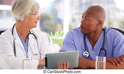 Mature doctor talking with a nurse in front of a touchscreen