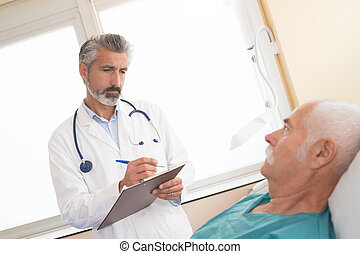 mature doctor talks with sick senior man at the hospital