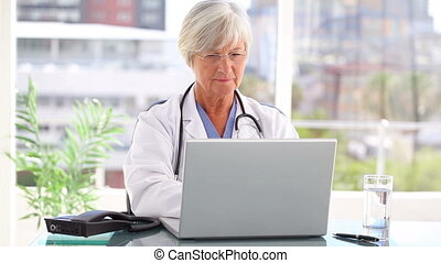 Mature doctor using a laptop