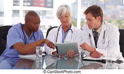 Mature doctor using a touchscreen with her colleagues in a...