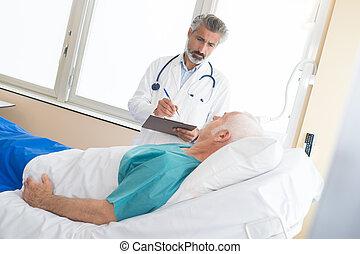 mature doctor visiting elderly patient in hospital room