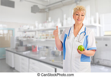 Mature doctor with apple at lab