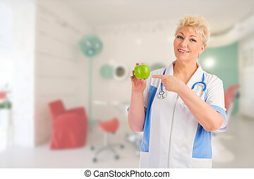 Mature doctor with apple at medical office