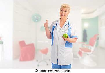 Mature doctor with green apple shows ok gesture