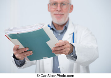 mature doctor with medical file