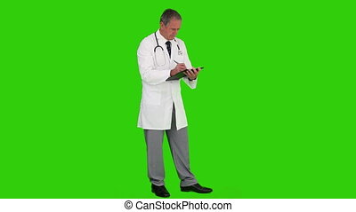 Chroma-key footage of a mature doctor writing something on his book