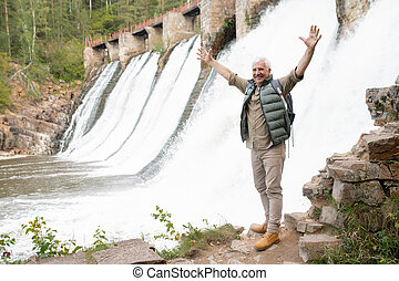 Mature ecstatic male hiker with raised arms standing on rock by waterfalls