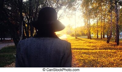 Mature elegant woman in a coat and a hat with their purchases bags in the park going through the sun at sunset. 3840x2160