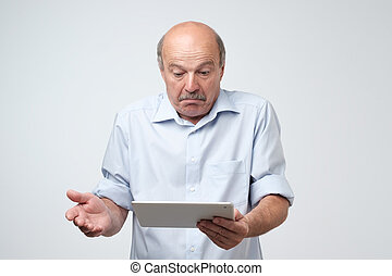 Mature european man using a digital tablet. He is puzzled and confused.