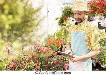 Mature farmer in hat and apron using digital tablet during work
