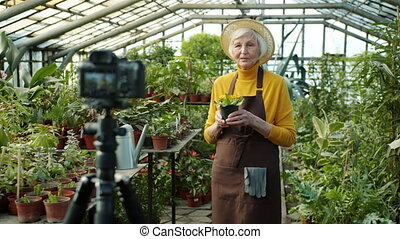 Mature farmer vlogger is recording video about floristry speaking holding plant standing in greenhouse and using professional camera. Technology and vlogging concept.