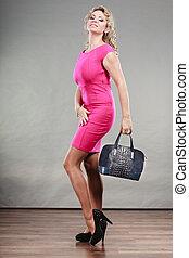 Mature fashion woman holds handbag
