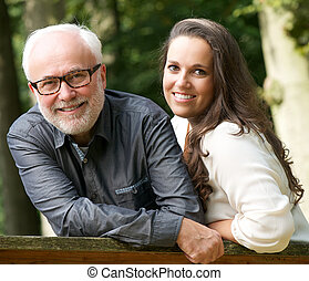 Mature father and young daughter smiling outdoors - Portrait...