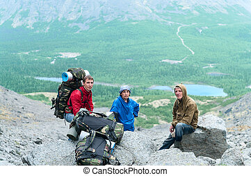 Mature father, mother and son hiking in mountains together