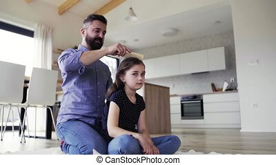 Mature father with small daughter indoors at home, combing...