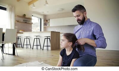 Mature father with small daughter indoors at home, plaiting...