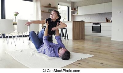 Mature father with small daughter on the floor indoors,...
