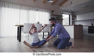 Mature father with small daughter playing indoors. - A...