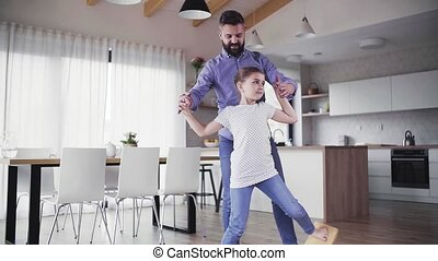 Mature father with small daughter playing indoors. Slow...