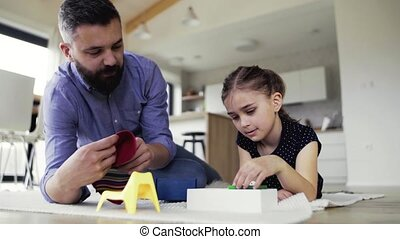 Mature father with small daughter sitting on sofa indoors,...