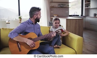 Mature father with small daughter sitting on sofa indoors, playing guitar.