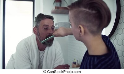 Mature father with small son combing hair and beard in the...