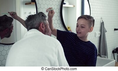 Mature father with small son combing hair in the bathroom in...
