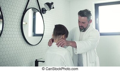Mature father with small son getting dressed in the bathroom...