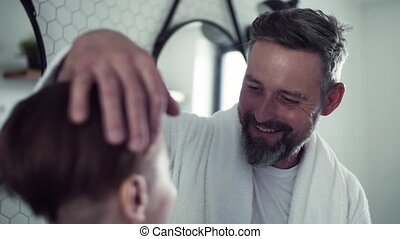 Mature father with small son in the bathroom in the morning,...
