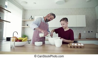 Mature father with small son indoors in kitchen, making...
