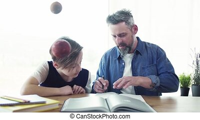 Mature father with small son sitting at table indoors, working on school project.
