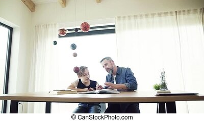 Mature father with small son sitting at table indoors,...