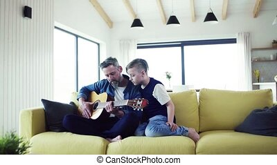 Mature father with small son sitting on sofa indoors,...
