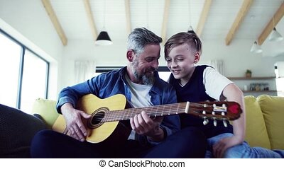 Mature father with small son sitting on sofa indoors, playing guitar.
