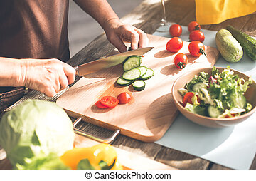 Mature female hands cutting vegetables on wooden board