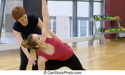 Mature female instructor is helping young woman to turn into right yoga position, slow motion.