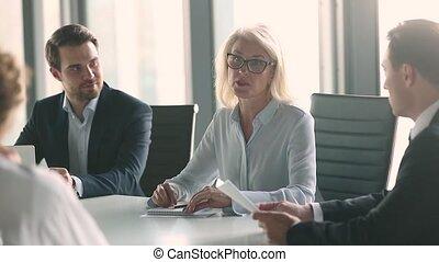 Mature female leader handshake male business partner over...