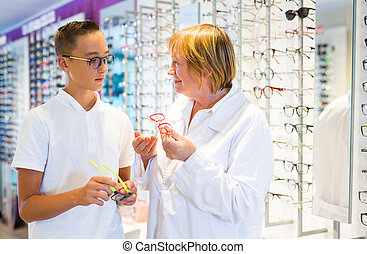 Mature female optician helping client to choose a spectacles