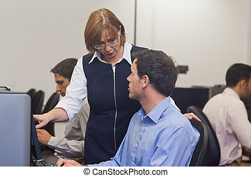 Mature female teacher talking to a student in computer class