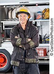 Mature Firefighter Standing Arms Crossed Against Firetruck