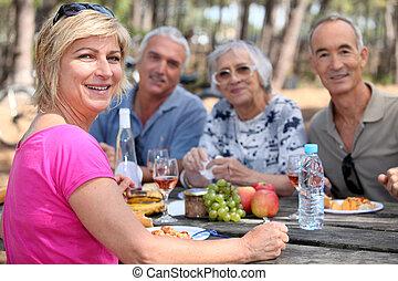 Mature friends eating alfresco