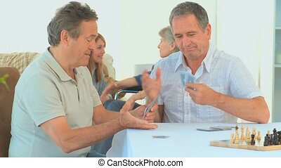 Mature friends playing cards while their wives are talking