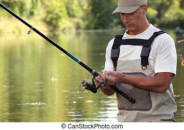mature gentleman fishing in river