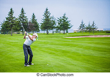 Mature Golfer on a Golf Course Taking a Swing in the Fairway