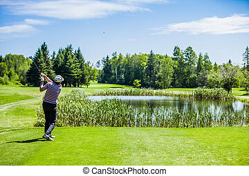 Mature Golfer on a Golf Course Taking a Swing on the Start.