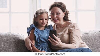 Mature grandma hug child granddaughter using smartphone at home