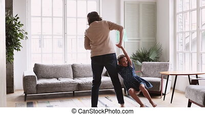 Mature grandmother dancing with energetic child girl in living room
